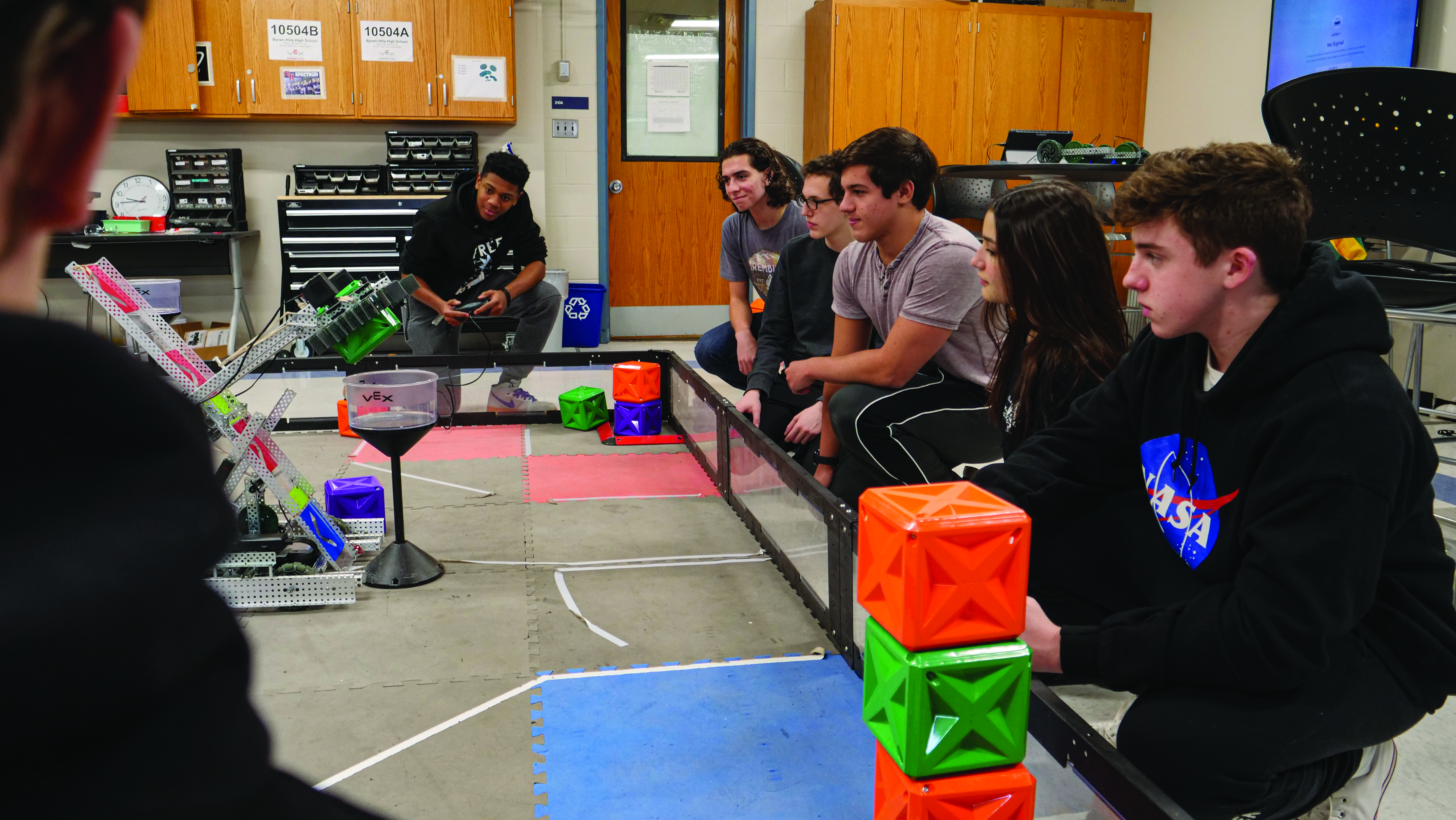 Byram Hills High School students manipulating a cube stacking robot.